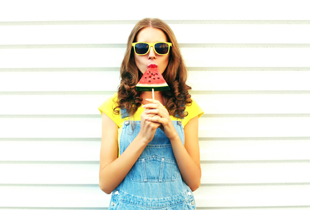 Fashion pretty woman eating a slice of watermelon in the form of ice cream on a white background Stock Photo