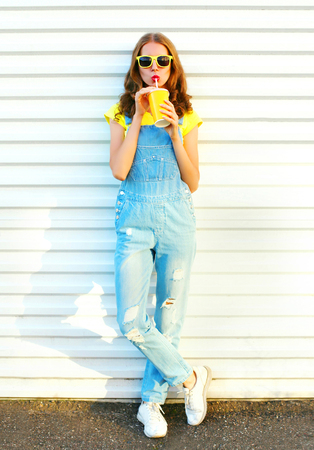 Fashion pretty young woman drinks a juice from cup over a white background