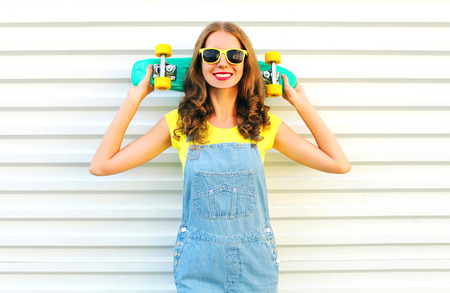 Fashion smiling cool girl with a skateboard over a white background