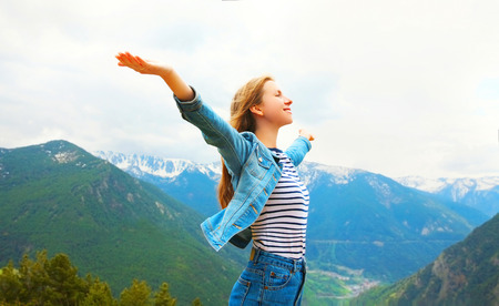 Travel happy woman enjoys fresh air mountains raises hands up, view of Spain landscape background Stock Photo