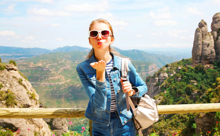 Travel young woman sends an air kiss on mountains Spain background Stock Photo