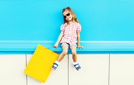 Fashion cool kid with shopping bag on a colorful blue background