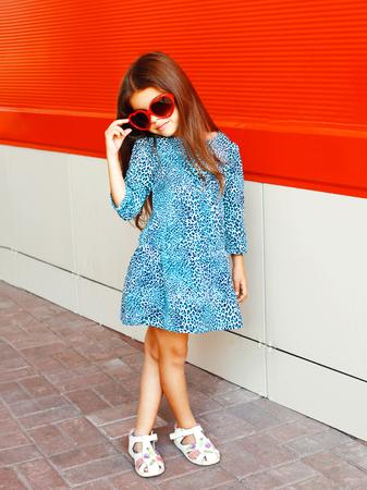 Moda hermosa niña niño llevaba un vestido de leopardo con gafas de sol sobre un fondo rojo Foto de archivo - 81778530