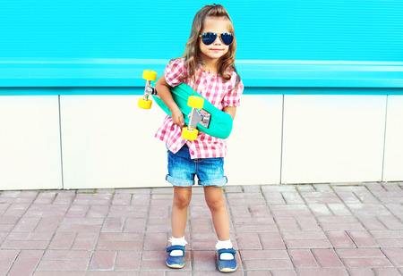 Fashion child holds skateboard in the city on a colorful blue background