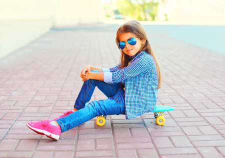 Fashion child little girl sitting on the skateboard in the city Stock Photo