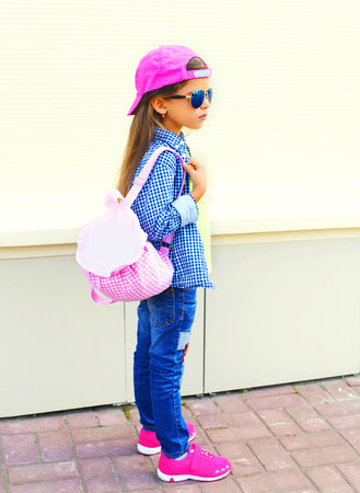 Fashion kid little girl wearing a baseball cap and backpack in the city on a white background Stok Fotoğraf