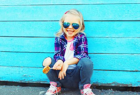 Glückliches lächelndes Kind des kleinen Mädchens des Modeporträts mit einem Lutscherstock, der Spaß hat