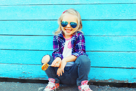 Fashion portrait happy smiling little girl child with a lollipop stick having fun