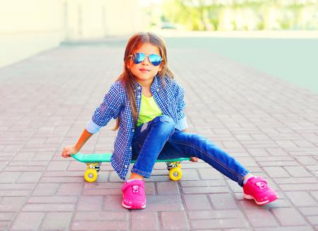 Fashion portrait little girl child sitting on skateboard in the city
