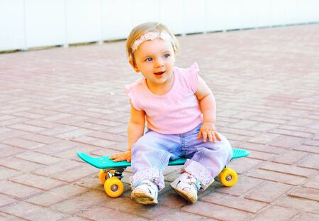 Funny baby sitting on the skateboard in the city