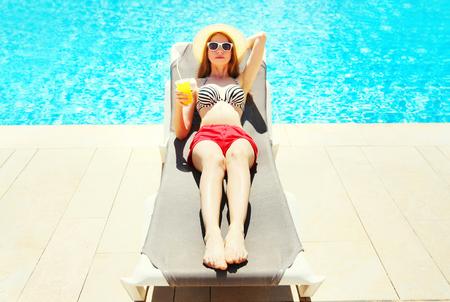여름 휴가 - 예쁜 여자 푸른 물 풀 배경 위에 deckchair에 컵에서 주스와 함께 쉬고