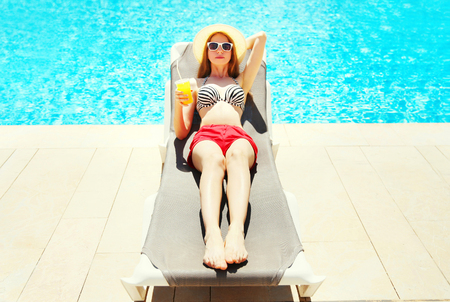 Summer holidays - pretty woman resting with juice from cup on a deckchair over a blue water pool background