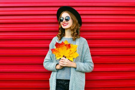 赤の背景に葉の黄色のカエデとファッション秋の肖像画笑顔女性 写真素材