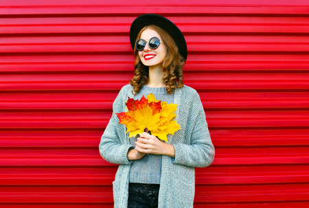 Fashion autumn portrait smiling woman with yellow maple leaves on a red background Standard-Bild