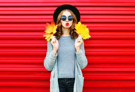 Fashion autumn portrait woman with yellow maple leaves on a red background