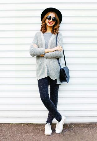 白の背景に黒のハンドバッグとはかなり笑顔の女性をファッションします。