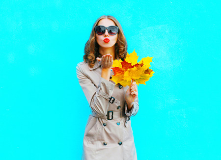 Fashion woman with autumn yellow maple leaves sends an air kiss on a blue background Stock Photo