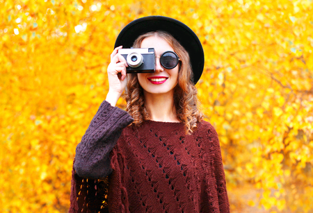 Autumn fashion smiling woman with retro camera in black round hat, knitted poncho