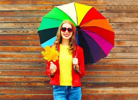 Lächelnde Frau des Porträts mit buntem Regenschirm im Herbst mit Ahornblättern über hölzernem Hintergrund Standard-Bild - 87235630