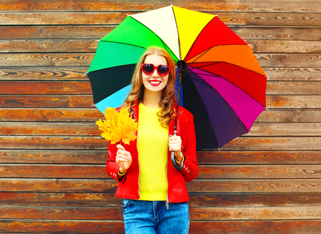 Portrait smiling woman with colorful umbrella in autumn with maple leaves over wooden background