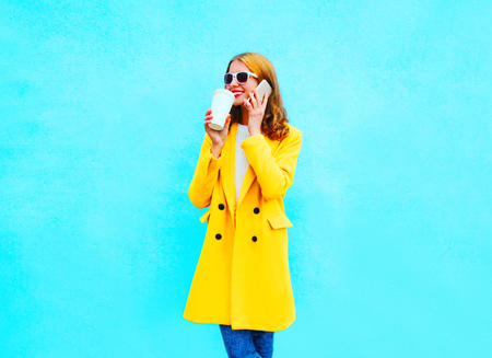 Fashion pretty smiling woman talks on a smartphone with cup of coffee on a colorful blue background