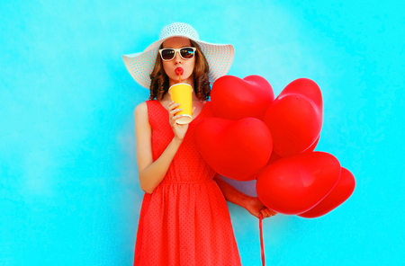 Portrait woman in summer hat drinks juice from cup with red an air balloons on blue background Stok Fotoğraf