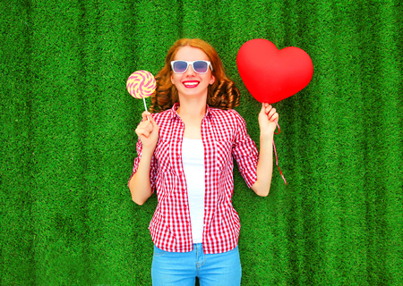 Happy woman holds a red air balloon in the shape of a heart, lollipop candy lies on the grass Stock Photo