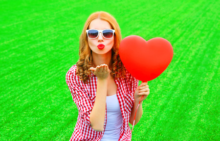 Portrait woman sends an air kiss with red balloon in the shape of a heart on the grass