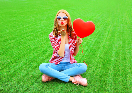 Pretty woman sends an air kiss with red balloon in the shape of a heart on the grass
