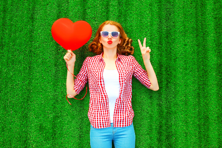Young pretty woman with red an air balloon in the shape of a heart lies on the grass Stock Photo