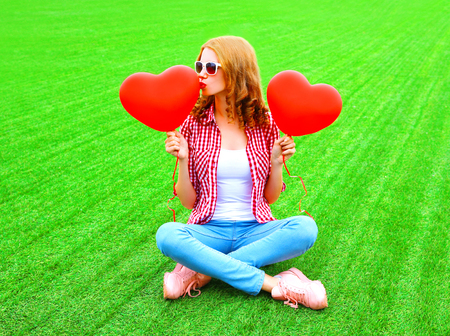 Young woman kisses an air red balloon in the shape of a heart on the grass