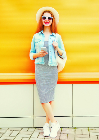 Fashion cool girl is using the smartphone in the city on a orange background Stock Photo