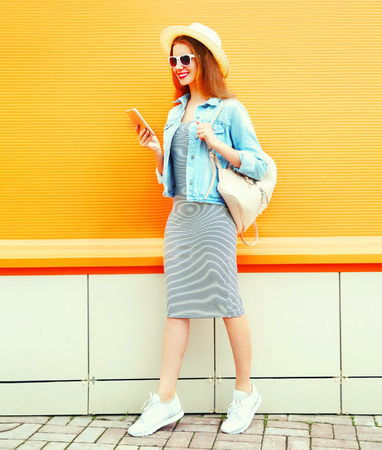 Fashion cool girl is using the smartphone walking in the city on orange background Stock Photo