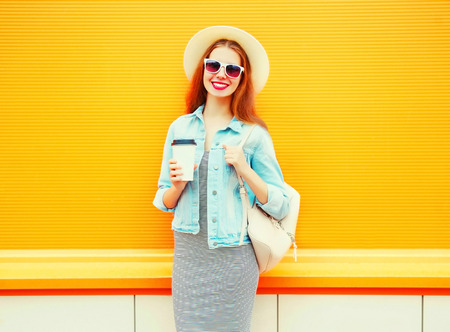 Fashion pretty smiling woman with a coffee cup on a orange background