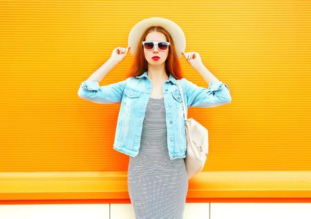 Fashion pretty woman in a straw hat on a orange background
