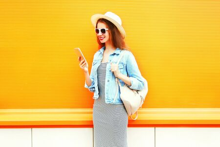 Fashion smiling cool girl is using the smartphone in the city on a orange background