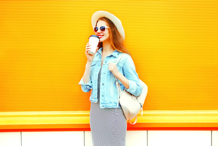 Fashion smiling woman drinks a coffee on a orange background