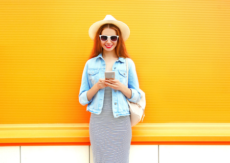 Fashion smiling woman is using the smartphone in the city on a orange background