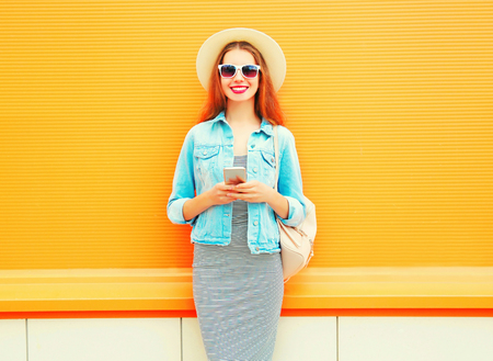 Fashion smiling woman is using the smartphone in the city on orange background Stock Photo