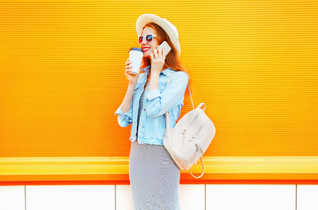 Fashion smiling woman talks on a smartphone holds coffee cup on a orange background  Stock Photo