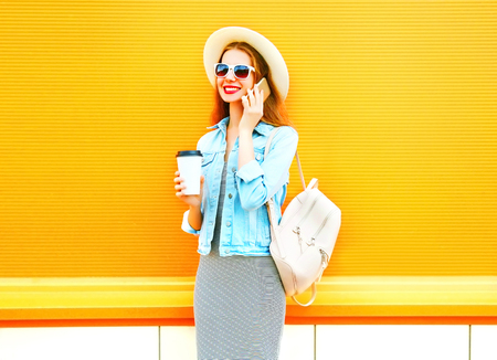Fashion smiling woman talks on a smartphone with coffee cup on a orange background