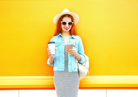 Fashion smiling woman using a smartphone holds coffee cup on a orange background Stock Photo