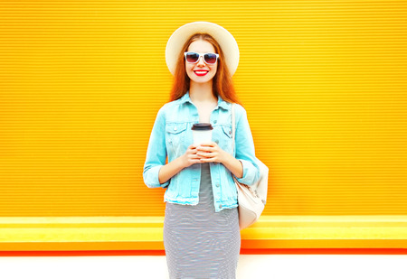 Fashion smiling woman with coffee cup on a orange background