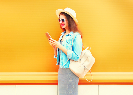 Fashion smiling young girl is using the smartphone in the city on a orange background