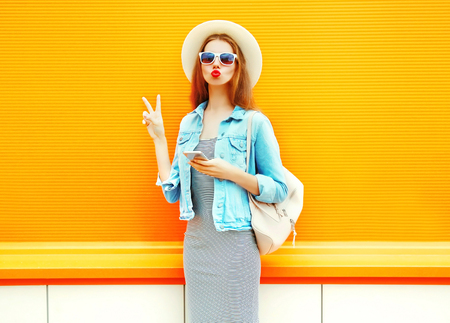 Fashion young woman with red lips is using the smartphone in the city on a orange background