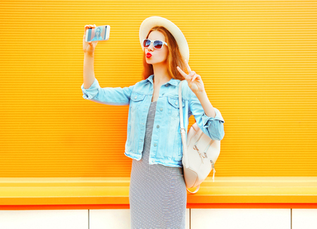 young woman takes a picture self portrait on a smartphone on orange background Stock Photo