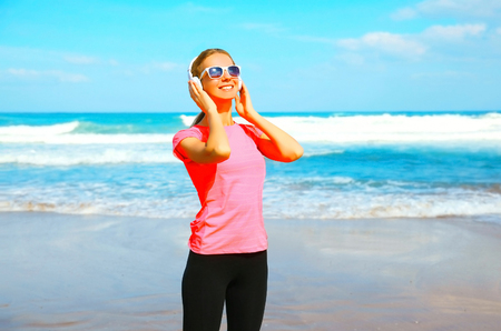 Fitness smiling woman listens to music in wireless headphones on the beach on a summer day 版權商用圖片