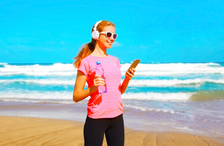 Fitness woman listens to music in wireless headphones with smartphone on the beach