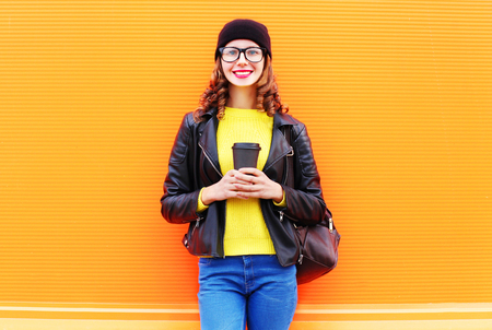 Fashion young smiling pretty young woman with coffee cup wearing a black hat, rock jacket over colorful orange background Stock Photo