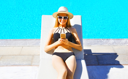 summer holidays - happy young woman in hay lying using smartphone on a deckchair over a blue water pool background